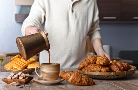 Breakfast with black coffee, freshly baked waffles and croissants . Old copper coffee maker . Fresh hot coffee is poured into the cup .