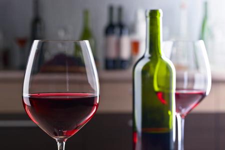 ボトル、キッチン テーブルの上の赤ワインのグラス。前景に焦点を当てます。 写真素材