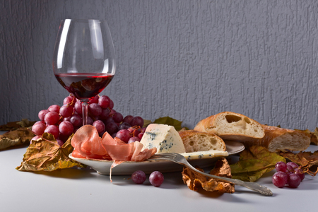 Red wine with snack and grapes . Blue cheese , prosciutto and bread on the kitchen table . Dried grape leaves . Stock Photo