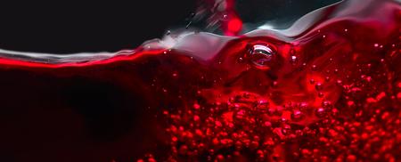 赤黒の背景にワインは、水しぶきを抽象化します。マクロ撮影します。