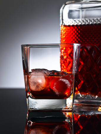 Whiskey with ice on a reflective background
