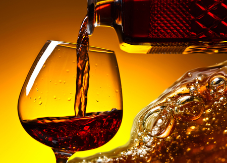 Cognac poured into a glass on a yellow background Stock Photo