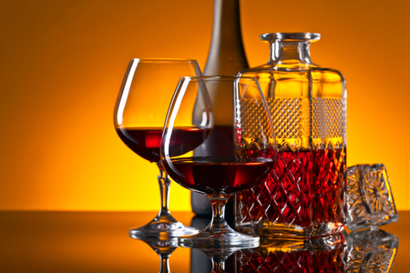 Two glasses of brandy on the reflective background Stock Photo