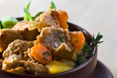 irish easter: Homemade beef stew with carrots and potatoes in ceramic pot . The dish is decorated with leeks and thyme .