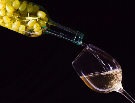 White grape in bottle and glass of wine on black background Stock Photo