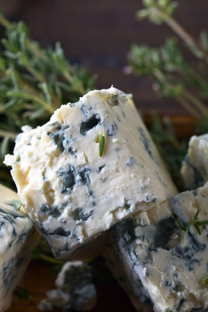 Blue cheese and branches of thyme on a wooden table .