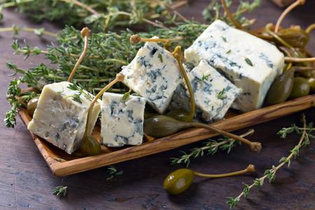 ブルー チーズ、ケッパー、木製のテーブルにタイムの枝。 写真素材