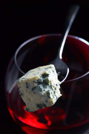 roquefort: Blue cheese on a fork and glass of red wine .