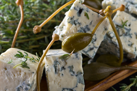 Blue cheese , capers and branches of thyme on a wooden table . Stock Photo