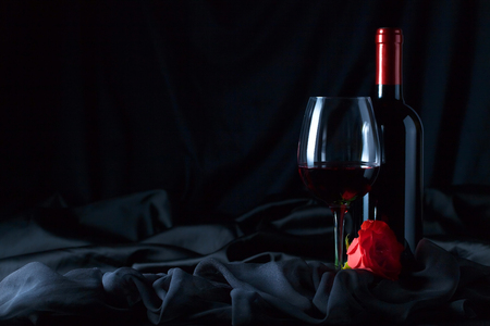 Bottle and glass of red wine  with red rose on  black background.