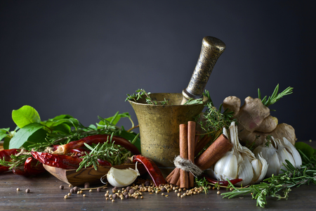 Different herbs and spices on a wooden table . Old copper mortar with spices . Stock Photo