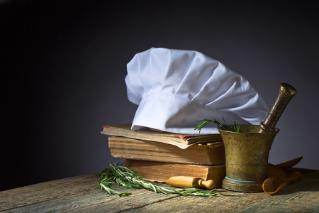 Old copper mortar with rosemary. Culinary books , chef hat and wooden spoons . Kitchen accessories on the old wooden table . 版權商用圖片