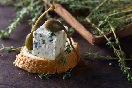 roquefort: Blue cheese , capers and branches of thyme on a wooden table . Stock Photo