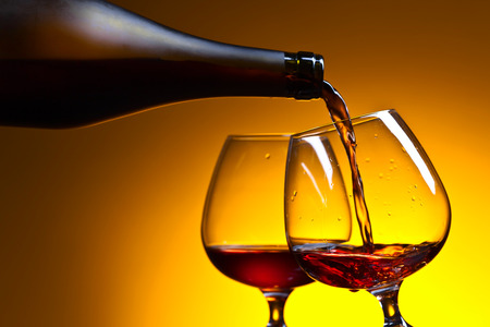 snifter: Cognac poured into a glass on a yellow background Stock Photo
