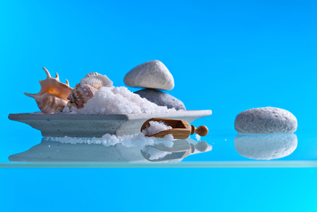 Sea salt on a glass table with stones and shells . Blue background with copy space. Stock Photo