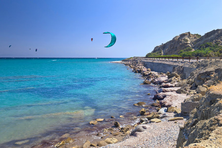 Road on a sea shore.Greece, Rhodes, kiting in Mediterranean sea . Sunny summer day .