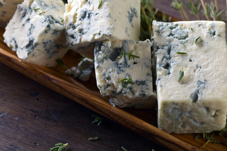 roquefort: Blue cheese and branches of thyme on a wooden table .
