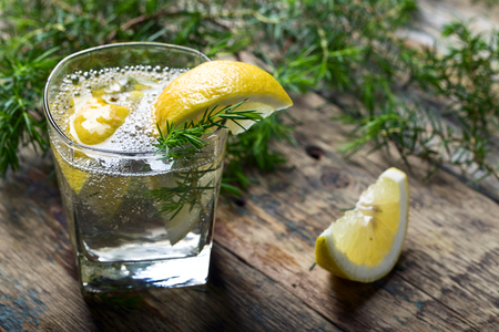 enebro: Cocktail with blue gin , tonic and lemon on a old wooden table . Alcoholic drink with lemon slices and juniper branch. Foto de archivo