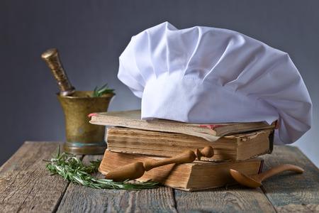 Alte Kupfermörtel mit Rosmarin. Kulinarische Bücher, Kochmütze und Holzlöffel. Küchenzubehör auf dem alten Holztisch. Standard-Bild