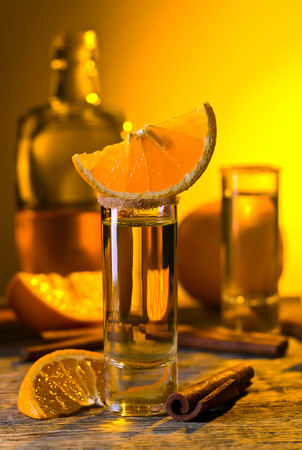 Gold tequila with orange and cinnamon on old wooden table . Stock Photo