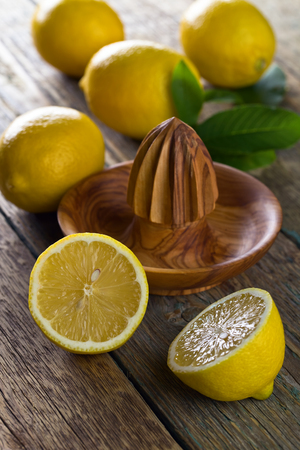 Ripe lemons and squeezer on a old wooden table .