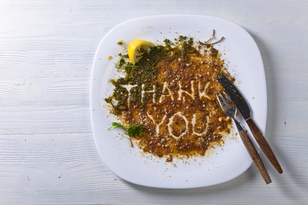 Dirty plate and Cutlery on the table after lunch . The view from the top .The words thank you . Stock Photo