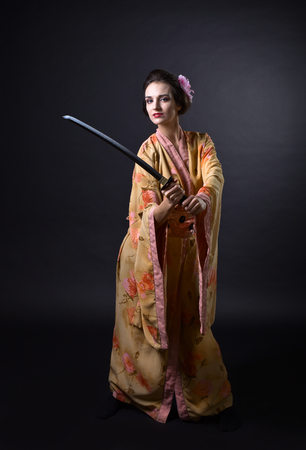 Beautiful woman in traditional japanese kimono with katana on a black background. Professional makeup and hair.