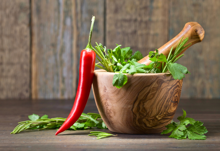 spice: Red pepper and wooden mortar with rosemary, coriander, thyme and parsley.