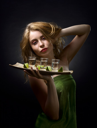 Attractive blonde woman with glasses of gold tequila and lime in hand . Beautiful professional  makeup and hair .