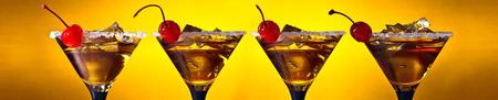 Four Martini with cherry and ice on a yellow background.