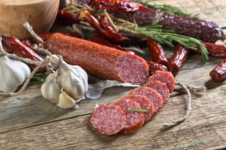 Smoked salami on a old wooden table. Sausages with rosemary , garlic and pepper. Stock Photo