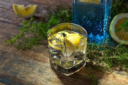 enebro: Cóctel con gin azul, tónico y limón en una vieja mesa de madera. Bebida alcohólica con rodajas de limón y rama de enebro. Foto de archivo