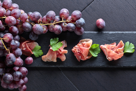 Jamon serrano with parsley and grape on a black table . Healthy organic food .