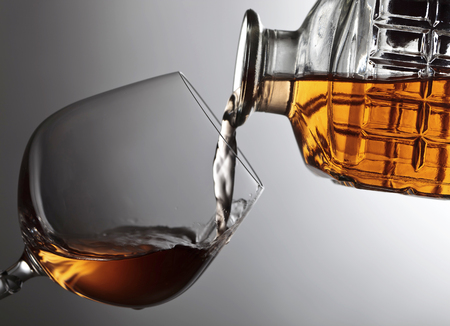 snifter: Glass filled with brandy from the jug .Copy space for text.