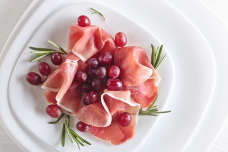 Jamon serrano with rosemary and grape on a white plate . Healthy organic food .