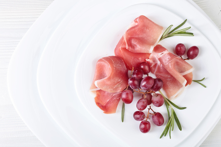 Jamon serrano with rosemary and grape on a white plate . Healthy organic food .Copy space for your text .