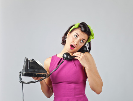 Beautiful brunette woman in pin up style with perfect hair and make up speaking via vintage phone.Expressive facial expressions.