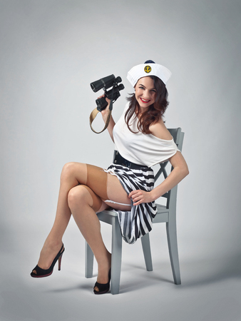 Beautiful woman in pin up style with perfect hair and make up in sailor costume .Expressive facial expressions.