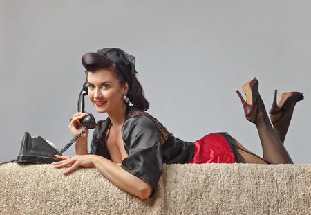 아름 다운 여자 핀 완벽 한 머리 스타일 및 빈티지 전화를 통해 말하기를 확인합니다. 표현 표정입니다. 스톡 콘텐츠