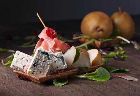 blauwe kaas met prosciutto en peer op een oude houten tafel