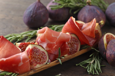 Prosciutto with figs and rosemary on a old wooden table.
