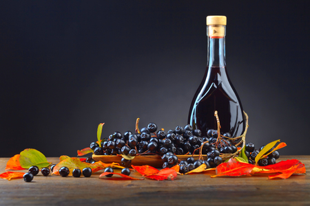 Black chokeberry (aronia melanocarpa) with bottle of juice and  autumn leaves on wooden table. Stock Photo