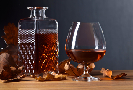 snifter: Brandy and dried up oak leaves on a old wooden table.