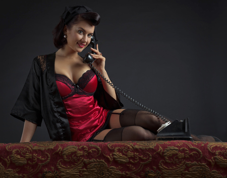 Beautiful woman with perfect hair and make up speaking via vintage phone . Copy space for your text.