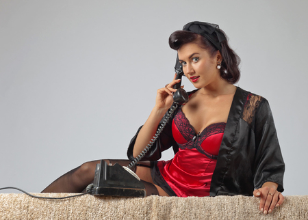 Beautiful woman with perfect hair and make up speaking via vintage phone.Copy space for your text.