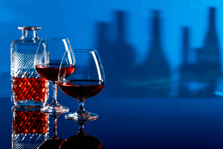 Two glasses of brandy on a black reflective background.
