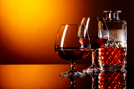 snifter: Two glasses of brandy on a black reflective background.