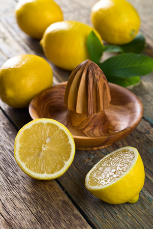 Juicy ripe lemons and old wooden squeezer . Stock Photo