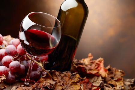 ガラスと赤のボトル ブドウを持つテーブルでワインし、ブドウの葉を乾燥します。