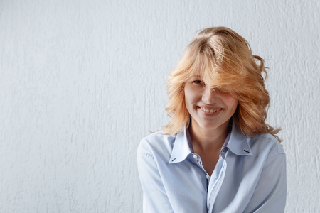 Young cute curly blonde in blue shirt .